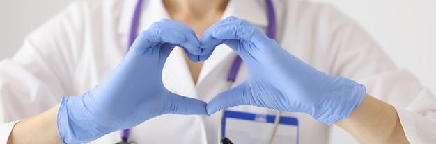 サージカルマスクを着用した医師が両手で心臓を見せます