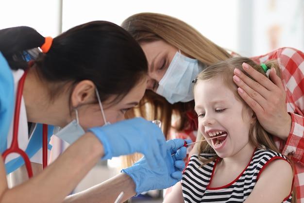 Врач в защитной медицинской маске берет мазок из ротовой полости у маленькой девочки с ватным тампоном