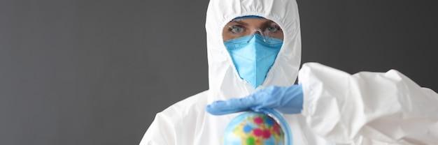 世界的なパンデミック・コビッドの概念を保持している防護服と眼鏡の医師