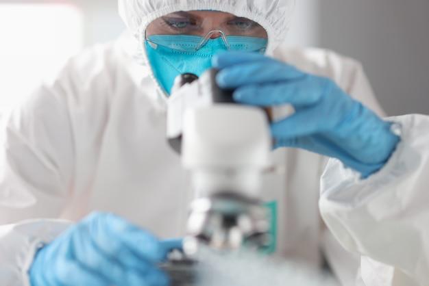 보호 복과 안경 의사가 현미경을 통해 보인다. 새로운 백신 개발 개념