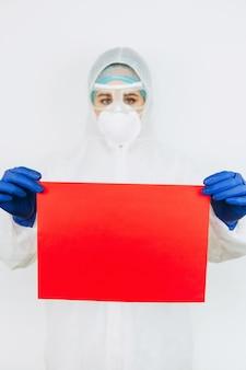 防護服と手袋の医師は、白地に赤い紙のシートを保持しています。医者はコロナウイルスと戦っています。 covid-19ウイルス。