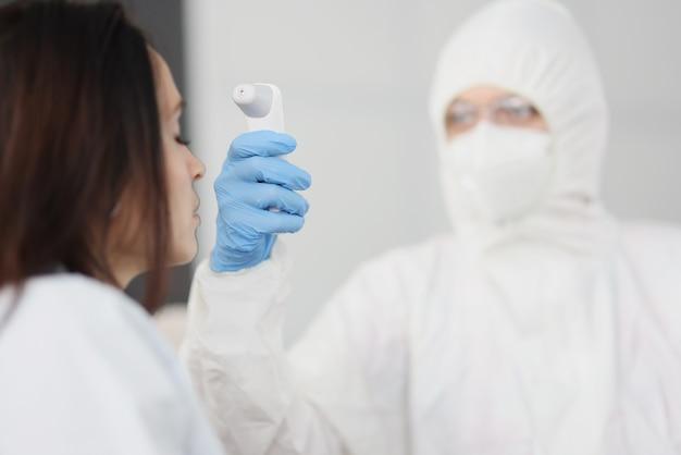 防護服と手袋をはめた医師が人の体温を測定します