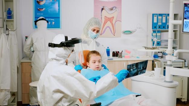 Covisd-19パンデミックでタブレットを使用した治療を説明する子供の患者の母親と歯のx線について話し合う防護服を着た医師。フェイスシールド、つなぎ服、マスク、手袋を着用した医療チーム