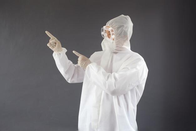 彼の左側のコピースペースを指している防護服を着た医師