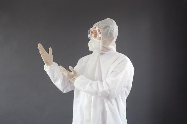 Доктор в защитном костюме, представляя руку, чтобы скопировать пространство на его стороне