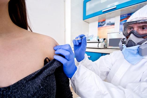 防護服の医師と女性患者にワクチンを与えるマスク。