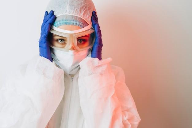 保護服、メガネ、ネオンの光で青い背景に手袋の医師。赤いネオンの医者のクローズアップの肖像画。疲れた男がコロナウイルスと戦っています。 covid 19