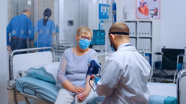 Covid-19 전염병 동안 현대 개인 병원이나 진료소에서 고혈압 환자를 검사하는 보호복을 입은 의사. 건강검진·의료질병진단 진단