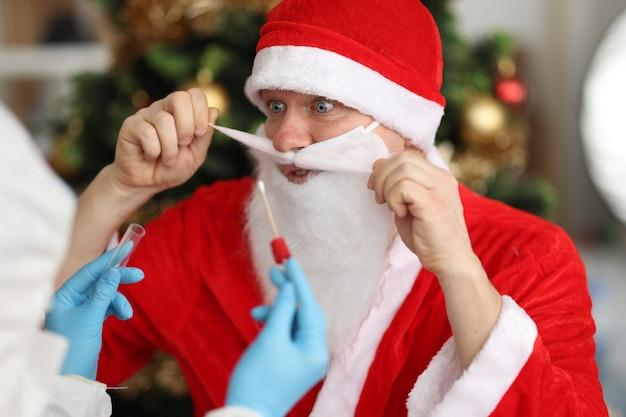 Доктор в резиновых перчатках берет мазок из носа pcr для санта-клауса возле елки