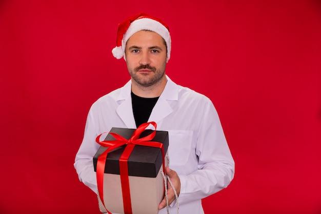 サンタクロースの帽子の医者はクリスマスプレゼントボックスを保持します