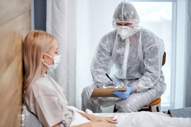 집에 앉아있는 동안 현재 건강 검사를 논의하는 양복과 아픈 환자의 의사. 코로나 바이러스 covid-19 대유행 및 자기 격리 격리 기간 동안 집에 머물러 있습니다. 의사에게 집중