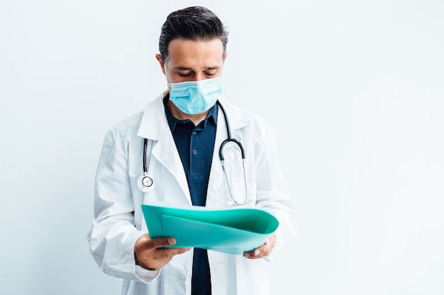 Врач в хирургической маске, белом халате, стетоскопе и синей папке с отчетом в руке.