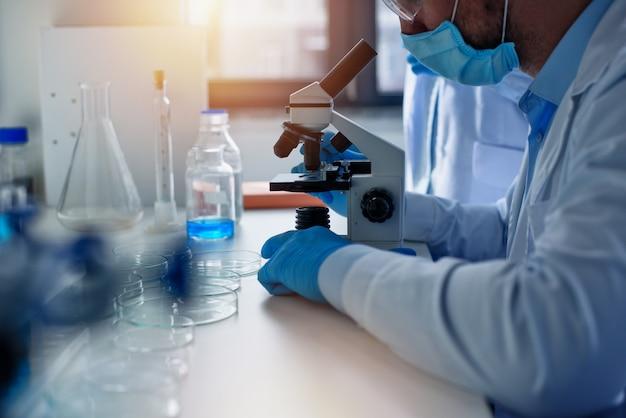 실험실의 의사는 현미경으로 샘플을 분석합니다. 제약 치료 개념.