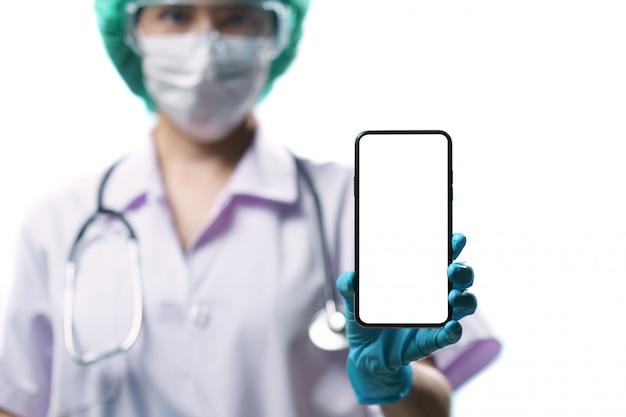 텍스트 빈 흰색 화면이 스마트 폰 들고 제복을 입은 의사. 코로나 바이러스, covid-19 발생 개념. 외딴.
