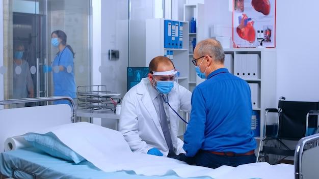 バイザーと保護服を着た医師が、コロナウイルスの流行中に引退した老人に心臓検査を行います。病気に専門的な治療を与える聴診器を使用した医療医療相談
