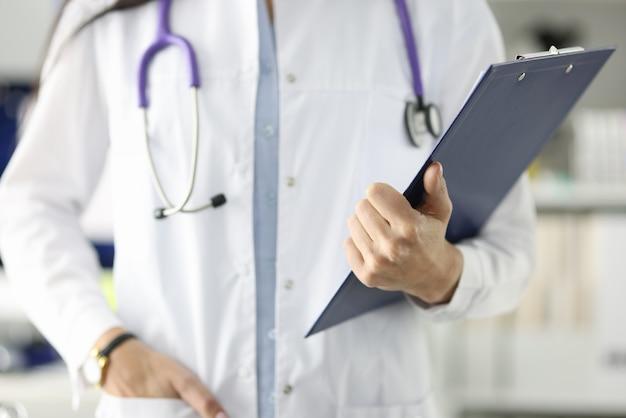 Врач в белом халате, держащий буфер обмена с документами в клинике, профессиональный медицинский совет