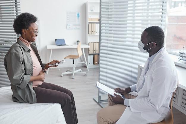 병원을 방문하는 동안 임신과 미래의 아기에 대해 환자에게 이야기하는 흰 가운을 입은 의사