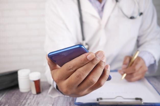 스마트 폰을 사용하고 처방전을 쓰는 흰 코트를 입은 의사