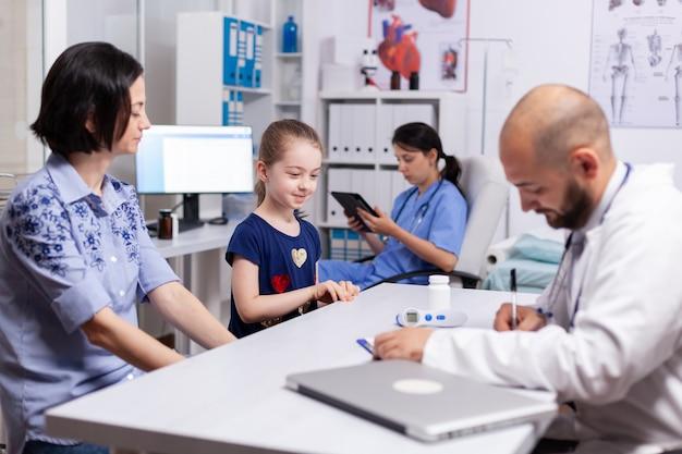 클리닉 사무실에서 건강 검진 중에 치료를 쓰는 백의를 입은 의사. 의료 병원에서 어머니와 질병에 대한 증상에 대해 논의하는 돌보는 소아과 의사