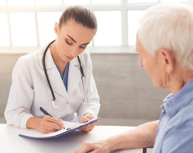 白い医療コートの医者は彼女の古い患者に聞いています。