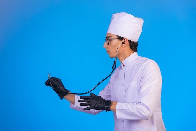 青の聴診器でチェックする白い医療制服の医者。