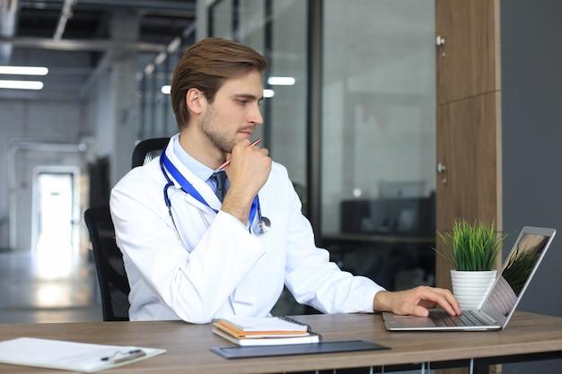 タブレットで患者の個人ファイルを読み取り、ラップトップにデータを書き込むスタトスコープを備えた白い医療ユニフォームの医師。
