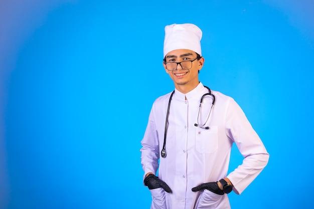 聴診器で白い医療服の医者は彼のポケットに手を入れて笑っています。