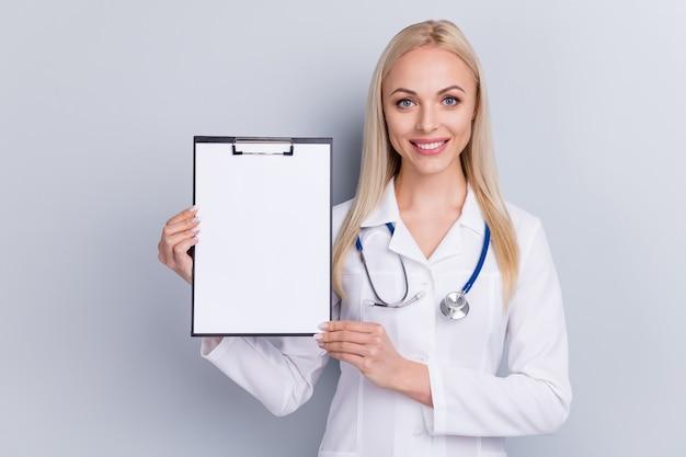 灰色で分離されたクリップボードを持つ白いスーツの医者