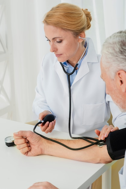 Doctor inflating blood pressure cuff