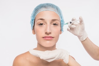 Doctor injecting in woman face
