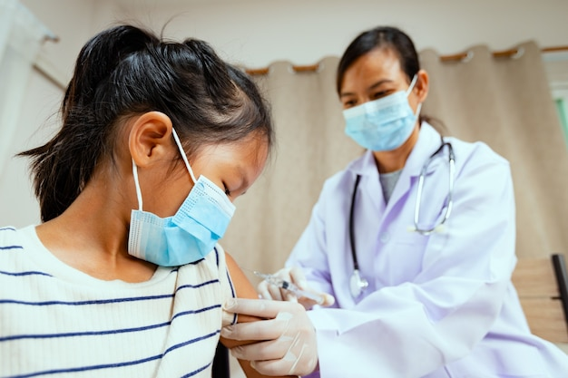 Доктор вводит вакцинацию на руку азиатской детской девочки. врач и ребенок-пациент в защитной маске для защиты от пандемии коронавируса covid-19. здравоохранение и медицинская концепция.