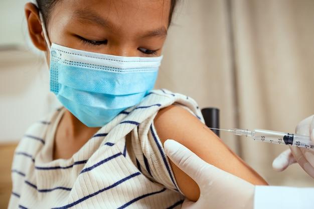 Доктор вводит вакцинацию на руку азиатской детской девочки. девочка в защитной маске для защиты от пандемии коронавируса covid-19. здравоохранение и медицинская концепция.