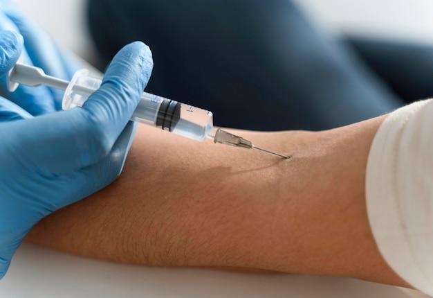 Доктор вводит вакцину в руку женщины