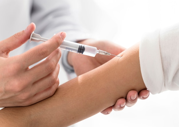 Doctor injecting the vaccine in a patient