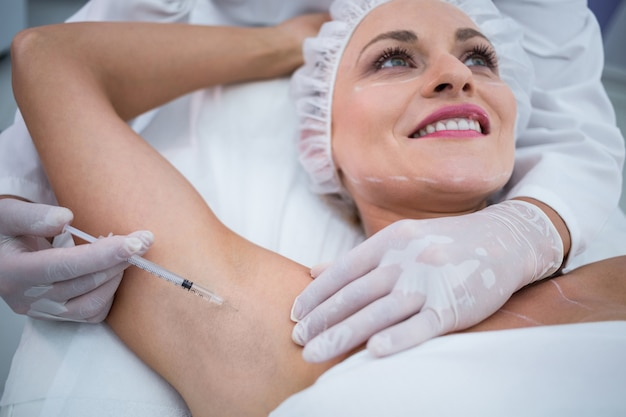 Doctor injecting woman on her arm pits
