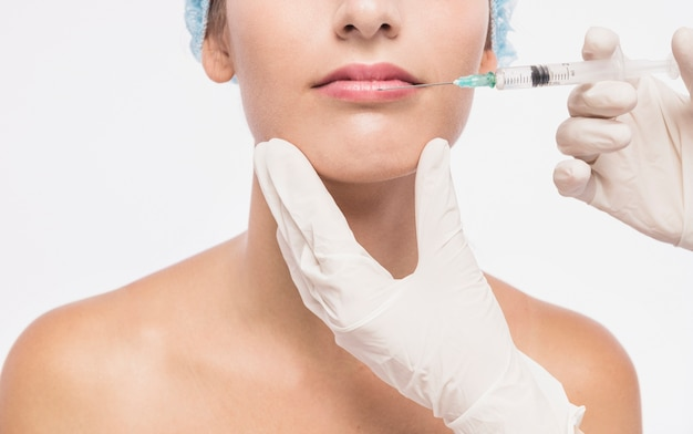Doctor injecting in woman lips