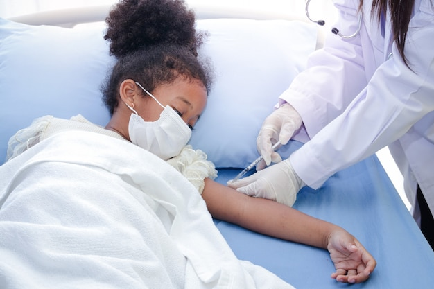 A doctor injects a vaccine in the arm of an african-american girl lying in a hospital bed