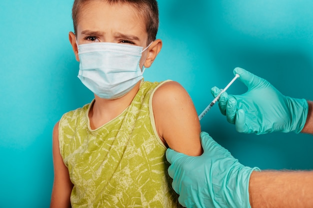 Doctor injects vaccine to a child against covid coronavirus