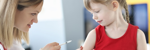 Doctor inoculates little girl in shoulder vaccination of children concept