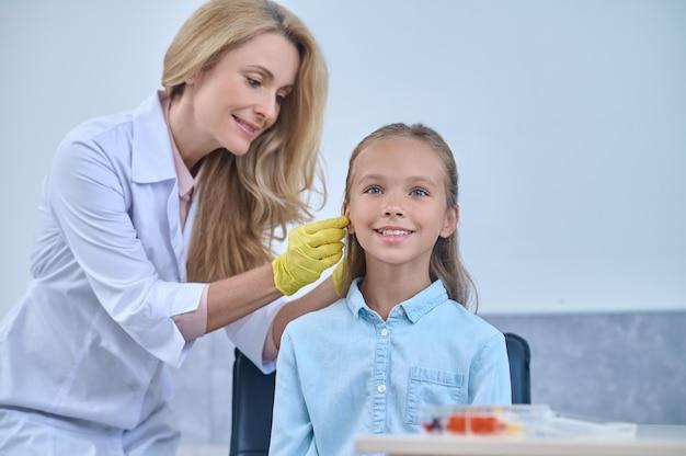 Врач вставляет слуховой аппарат в ушной канал пациента