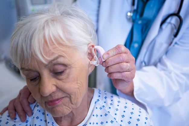 의사가 노인 환자의 귀에 보청기를 삽입