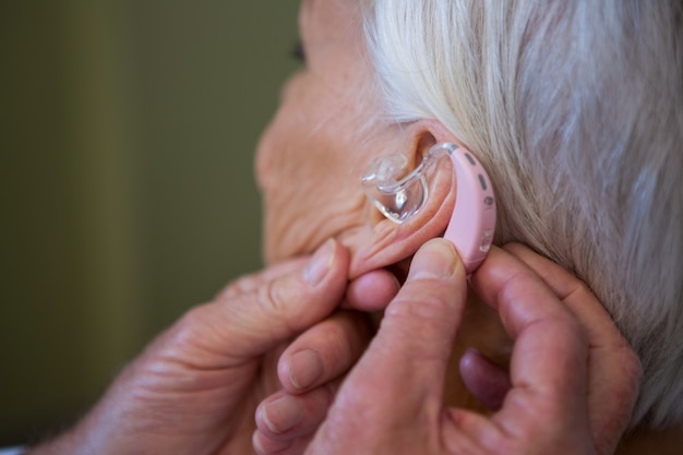 Doctor inserting hearing aid in senior patient ear