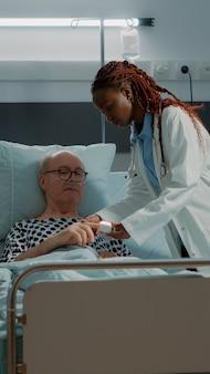 병원 병동에서 환자의 손에 산소 농도계를 설치하는 의사