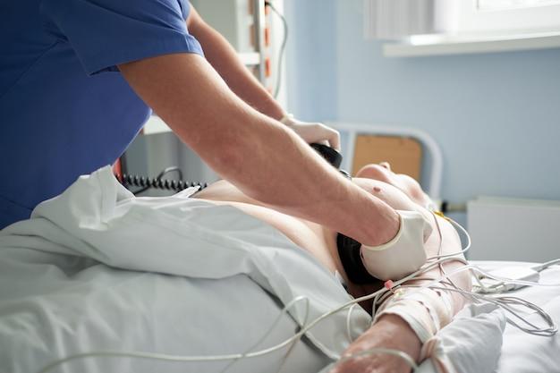 Врач-интенсивист выполняет дефибрилляцию для критического пациента