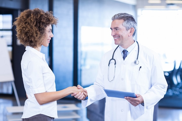 Doctor interacting and shaking hands with colleague in hospital