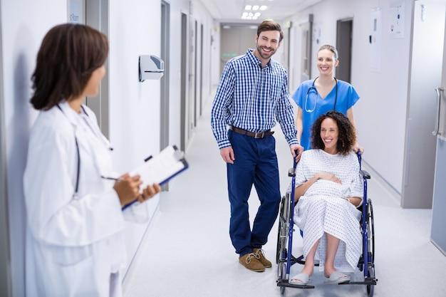 Доктор взаимодействует с беременной женщиной в коридоре