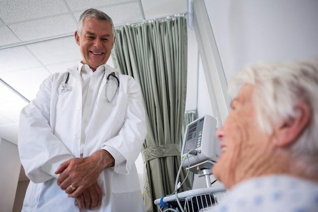 Врач взаимодействует со старшим пациентом в палате