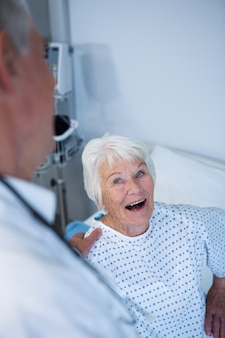 Doctor interacting with senior patient in ward
