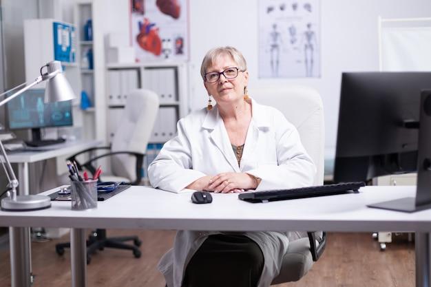 Врач взаимодействует онлайн с удаленными пациентами, сидящими за столом в частной больнице. уверенный портрет врача, дружелюбная женщина-терапевт позирует, глядя в камеру в медицинском кабинете