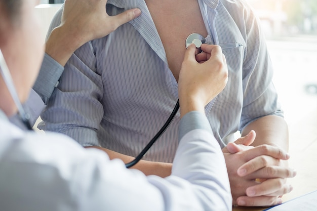 Врач проверяет грудь пациента с помощью стетоскопа, чтобы прослушать пульс пациента